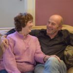 Happy Man and Woman sitting on sofa